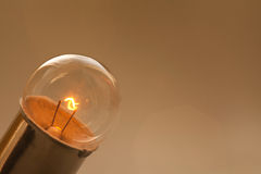 Glowing light bulb on gold brown background. Retro style lamp with ideal spherical surface and filament element. Macro Stock Images