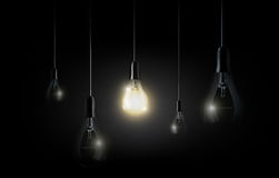 Glowing light bulb is hanging between a lot of turned off light bulbs on dark black background, copyspace, transparent vector. Glowing light bulb is hanging Royalty Free Stock Photos