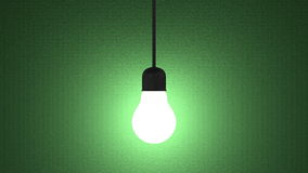 Glowing light bulb in lamp socket hanging on green Stock Images