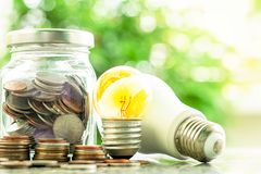 Glowing light bulb and led lamp with money coins in the glass ja. R against blurred natural green background for finance, saving energy and environment concept stock image
