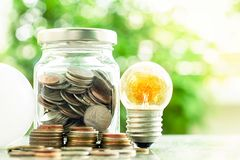 Glowing light bulb and led lamp with money coins in the glass ja. R against blurred natural green background for finance, saving energy and environment concept stock photography