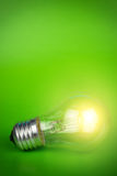 Glowing light bulb over green background Royalty Free Stock Photos