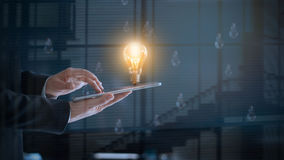 Glowing light bulb over labtop of businessman among others Royalty Free Stock Photo
