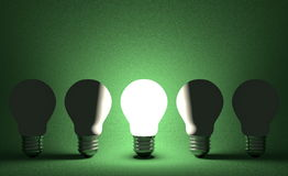 Glowing light bulb in row of switched off ones on green. Front view Stock Photos
