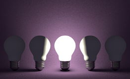 Glowing light bulb in row of switched off ones on violet. Front view Royalty Free Stock Photography