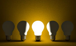 Glowing light bulb in row of switched off ones on yellow. Front view Stock Photos