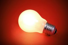 Glowing light bulb turned on. Over a orange background Stock Images