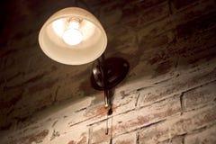 Glowing light bulb on wall stock photos