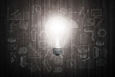 Glowing light bulb on wooden wall with drawing charts and graphs about business success strategy plan Stock Images
