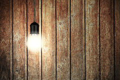 Glowing Light Bulb With Wooden Wall. Vintage Background Stock Photo