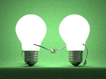 Glowing light bulbs handshaking on green Royalty Free Stock Images