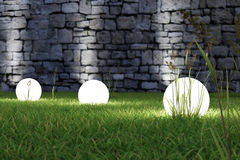 Glowing light in the grass. With old wall in background Stock Image