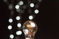 A glowing lightbulb on black blurred bokeh background photography Royalty Free Stock Photo
