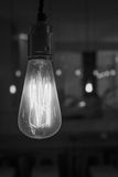 Glowing lightbulb dangling from the ceiling in black and white. Black and white close up of a glowing lightbulb dangling from the ceiling with the background royalty free stock images