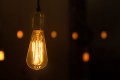 Glowing lightbulb dangling from the ceiling. Close up shot of an ambient glowing lightbulb taken in a restaurant royalty free stock image