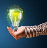 Glowing lightbulb in the hand of a businessman Stock Photography
