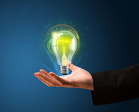Glowing lightbulb in the hand of a businessman Stock Photo