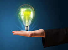 Glowing lightbulb in the hand of a businessman Royalty Free Stock Photo