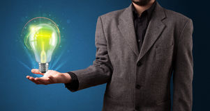 Glowing lightbulb in the hand of a businessman Royalty Free Stock Photography