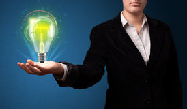 Glowing lightbulb in the hand of a businesswoman Royalty Free Stock Image
