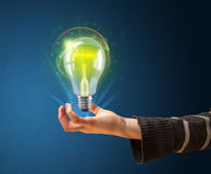 Glowing lightbulb in the hand of a woman Stock Image