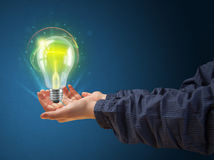 Glowing lightbulb in the hand of a woman Stock Images