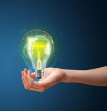 Glowing lightbulb in the hand of a woman Royalty Free Stock Photos