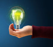 Glowing lightbulb in the hand of a woman Stock Photography