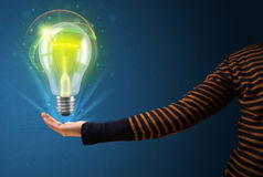 Glowing lightbulb in the hand of a woman Royalty Free Stock Photography