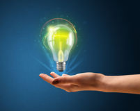Glowing lightbulb in the hand of a woman Stock Photos