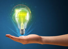 Glowing lightbulb in the hand of a woman Royalty Free Stock Images
