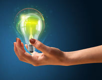 Glowing lightbulb in the hand of a woman Stock Photo
