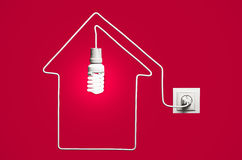 Glowing lightbulb in a house Stock Photography
