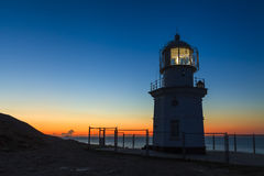 Glowing lighthouse against the night scenery. Royalty Free Stock Photos
