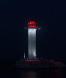 Glowing lighthouse at the entrance to the port Royalty Free Stock Photo