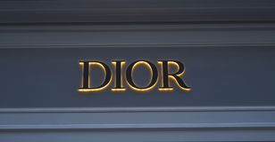 Glowing logo on the wall brand DIOR stock photography