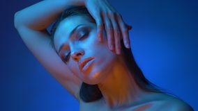 Glowing model with shiny makeup standing in blue neon lights putting hand over head watching into camera seriously. Glowing model with shiny makeup standing in stock video