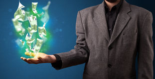 Glowing money in the hand of a businessman Stock Images