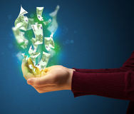 Glowing money in the hand of a woman Stock Photo