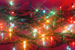 Glowing multicolored Christmas garlands reflected Stock Images