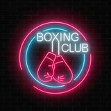 Glowing neon boxing club sign in circle frames on dark brick wall background. Fighting club neon signboard. Nightlife advertising symbol of sport facility on Royalty Free Stock Photo