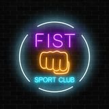 Glowing neon fighting fist sport club sign in circle frame on dark brick wall background. Boxing club neon signboard. Glowing neon fighting sport club sign in Royalty Free Stock Photos