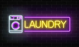 Glowing neon laundry signboard on dark brick wall background. Illuminated self-service washhouse. Glowing neon laundry signboard on dark brick wall background Royalty Free Stock Image