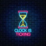 Glowing neon sign with hourglass and clock is ticking text. Call to action symbol of sandglass with cheering inscription. Glowing neon sign with hourglass and Royalty Free Stock Photography