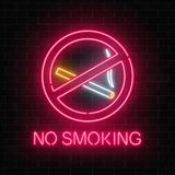 Glowing neon sign no smoking on dark brick wall of nightclub or bar. Ban on nicotine and smoke cigarettes. Stock Images
