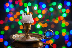 Glowing old candle in wintage candlestick on surface of mirror w Royalty Free Stock Photos