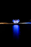 Glowing Olympic rings reflected in the harbor. Blue olympic rings during the 2010 Winter Olympic Games, Vancouver, Canada. Motion blurred zoom Royalty Free Stock Image