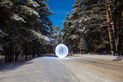 Glowing orb on the road, running on snow-covered pine forest Stock Image