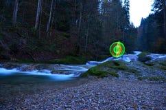 Glowing orb beside waterfall Royalty Free Stock Image