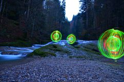 Glowing orbs beside waterfall Royalty Free Stock Photography